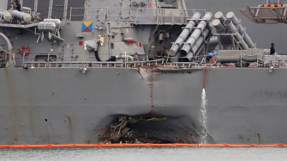 In this Tuesday, Aug. 22, 2017, filephoto, the damaged port aft hull of the USS John S. McCain, is visible while docked at Singapore's Changi naval base in Singapore. The focus of the search for the U.S. sailors missing after a collision between the USS John S. McCain and an oil tanker in Southeast Asian waters shifted Tuesday to the damaged destroyer's flooded compartments. (AP Photo/Wong Maye-E, File)