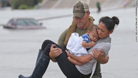 Houston SWAT officer Daryl Hudeck carries Catherine Pham and her son 13-month-old son Aidan to safety after they were rescued via boat from the flooding on Interstate 610 south in Houston on Sunday, August 27, 2017. (Louis DeLuca/The Dallas Morning News)