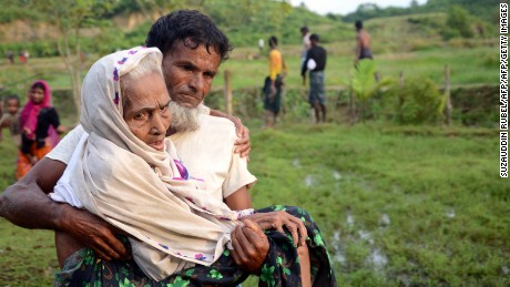 A Rohingya man carries his mother in Ukhiya, Bangladesh, after crossing the border from Myanmar.