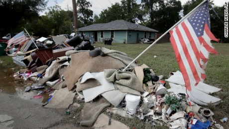 Tattered flags fly over a pile of water-soaked items as people clean up in a flood ravaged neighborhood Thursday, Aug. 31, 2017, in Houston. The city continues to recover from record flooding caused by Harvey. (AP Photo/Charlie Riedel)