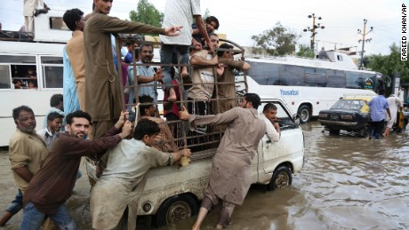 People push a vehicle after heavy rainfall in Karachi, Pakistan, Thursday, Aug. 31, 2017.
