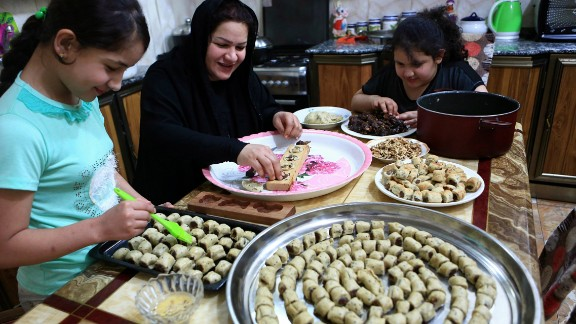 An Iraqi mother and her children prepare cookies for holiday in Basra, Iraq.