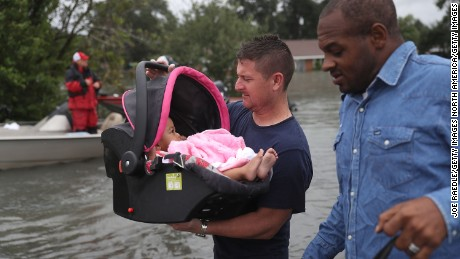 PORT ARTHUR, TX - AUGUST 30:  A rescue worker carries a baby to dry land after she was rescued from the flooding of Hurricane Harvey on August 30, 2017 in Port Arthur, Texas. Harvey, which made landfall north of Corpus Christi late Friday evening, is expected to dump upwards to 40 inches of rain in Texas over the next couple of days.  (Photo by Joe Raedle/Getty Images)