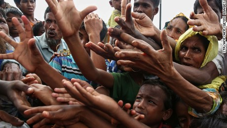 TOPSHOT - This August 30, 2017 photo shows Rohingya refugees reaching for food aid at Kutupalong refugee camp in Ukhiya near the Bangladesh-Myanmar border. The International Organization for Migration said August 30 that at least 18,500 Rohingya had crossed into Bangladesh since fighting erupted in Myanmar's neighbouring Rakhine state six days earlier.  / AFP PHOTO / STR        (Photo credit should read STR/AFP/Getty Images)