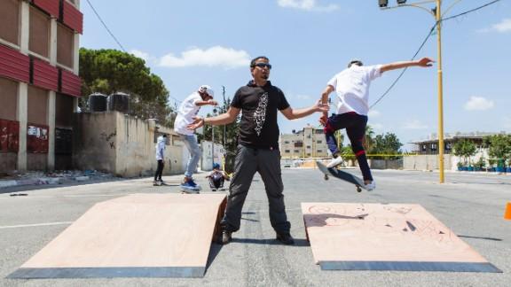 Children perform tricks on skateboards at the SkateQilya summer camp in the West Bank town of Qalqilya.