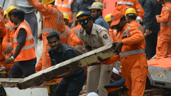Rescue workers and a policeman help clear debris as they look for survivors.