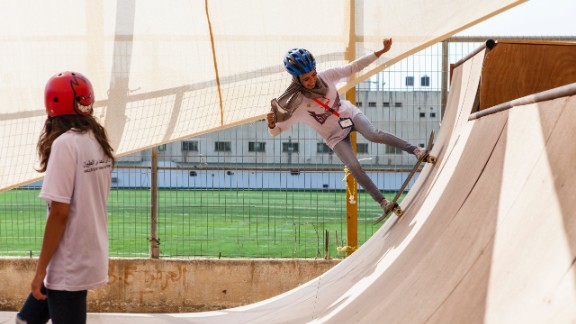 A young skateboarder takes on the ramp at the SkateQilya camp in the West Bank.