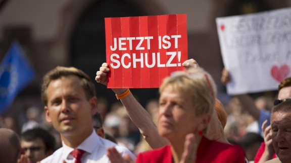 """An SPD supporter holds up a """"Now Is Schulz"""" poster at a campaign rally."""