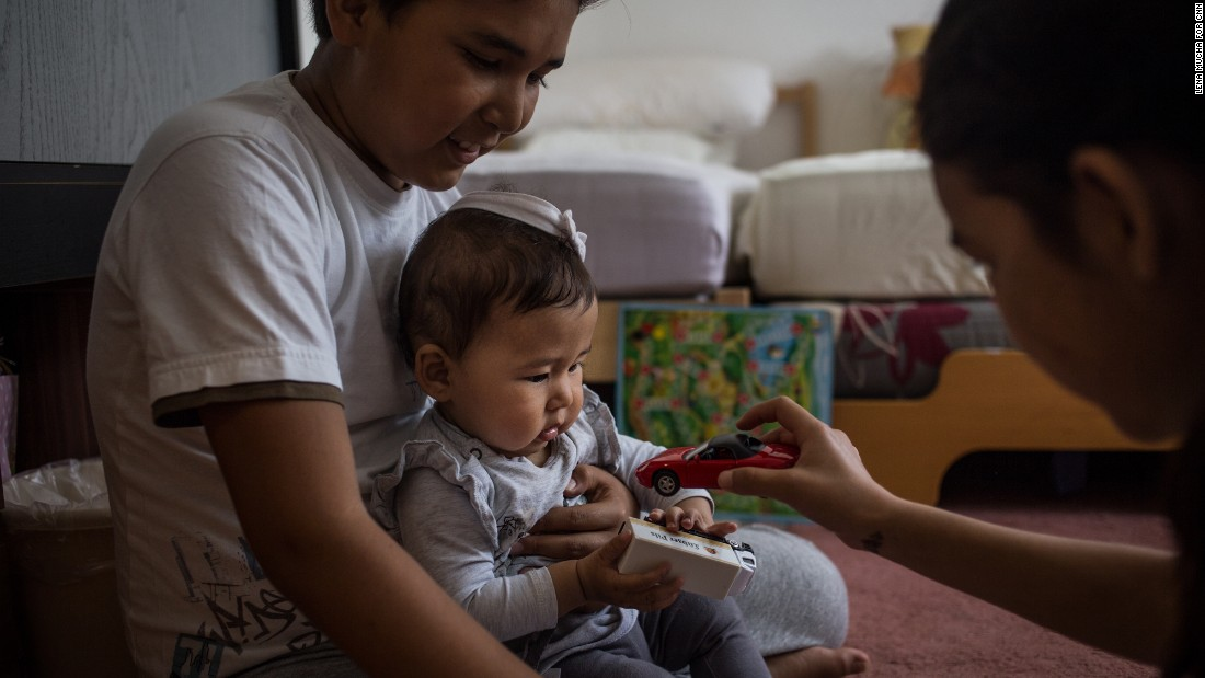 At their home in Altena, Yalda, 8 and Omit, 8, play together with 9-month-old Elena, all members of the Mohammadi family.