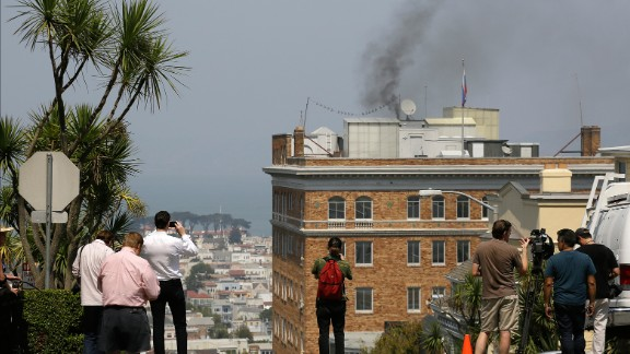 People stop to watch black smoke coming from the roof of the Consulate-General of Russia Friday, Sept. 1, 2017, in San Francisco. The San Francisco Fire Department says acrid, black smoke seen pouring from a chimney at the Russian consulate in San Francisco was apparently from a fire burning in a fireplace. The smoke was seen billowing from the consulate building a day after the Trump administration ordered its closure. (AP Photo/Eric Risberg)