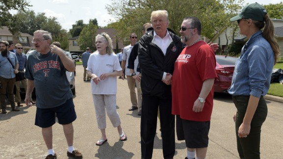 President Donald Trump and first lady Melania Trump talk with people impacted by Hurricane Harvey in a Houston neighborhood on Saturday.