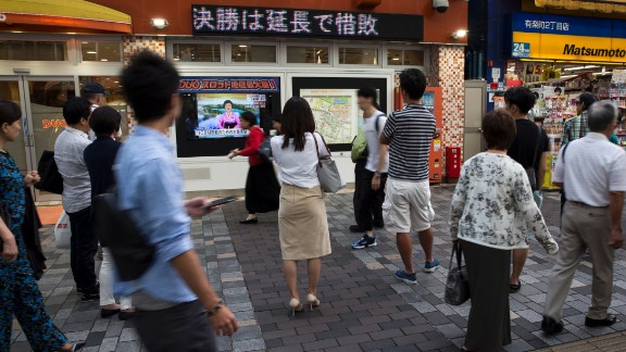 TOKYO, JAPAN - SEPTEMBER 03:  Pedestrians watch a monitor showing a news program reporting on North Korea