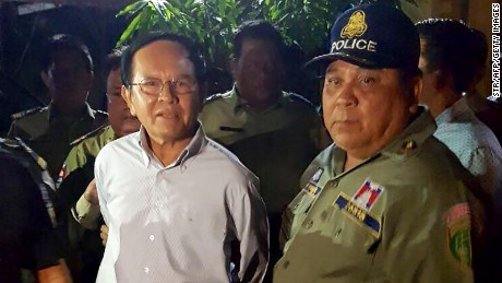 Cambodian opposition leader Kem Sokha is escorted by police at his home in Phnom Penh on September 3, 2017.