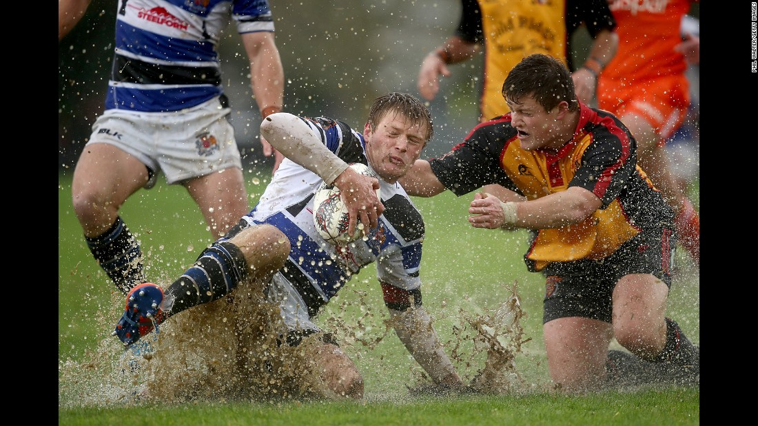 Wanganui rugby player Simon Dibben slides into the mud as Travis Scott tackles him in Paeroa, New Zealand, on Saturday, September 2.