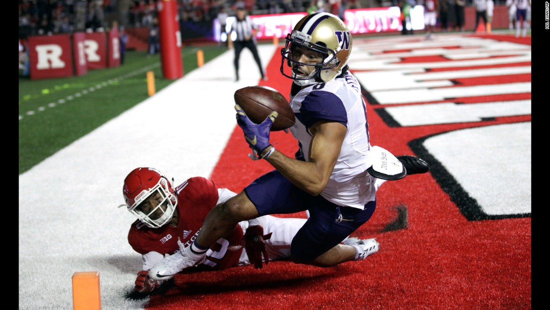 Washington wide receiver Dante Pettis pulls in a pass as he's defended by Rutgers cornerback Blessuan Austin during a college football game in Piscataway, New Jersey, on Friday, September 1. Pettis was ruled out of bounds on the play.