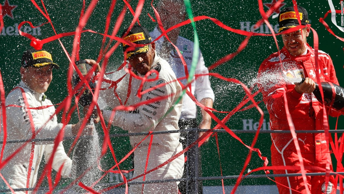 "Formula One driver Lewis Hamilton, center, celebrates <a href=""http://www.cnn.com/2017/09/03/motorsport/lewis-hamilton-wins-monza-formula-one-sebastian-vettel-ferrari/index.html"" target=""_blank"">his win in the Italian Grand Prix</a> on Sunday, September 3. Joining him on the podium were second-placed Valtteri Bottas, left, and third-placed Sebastian Vettel."