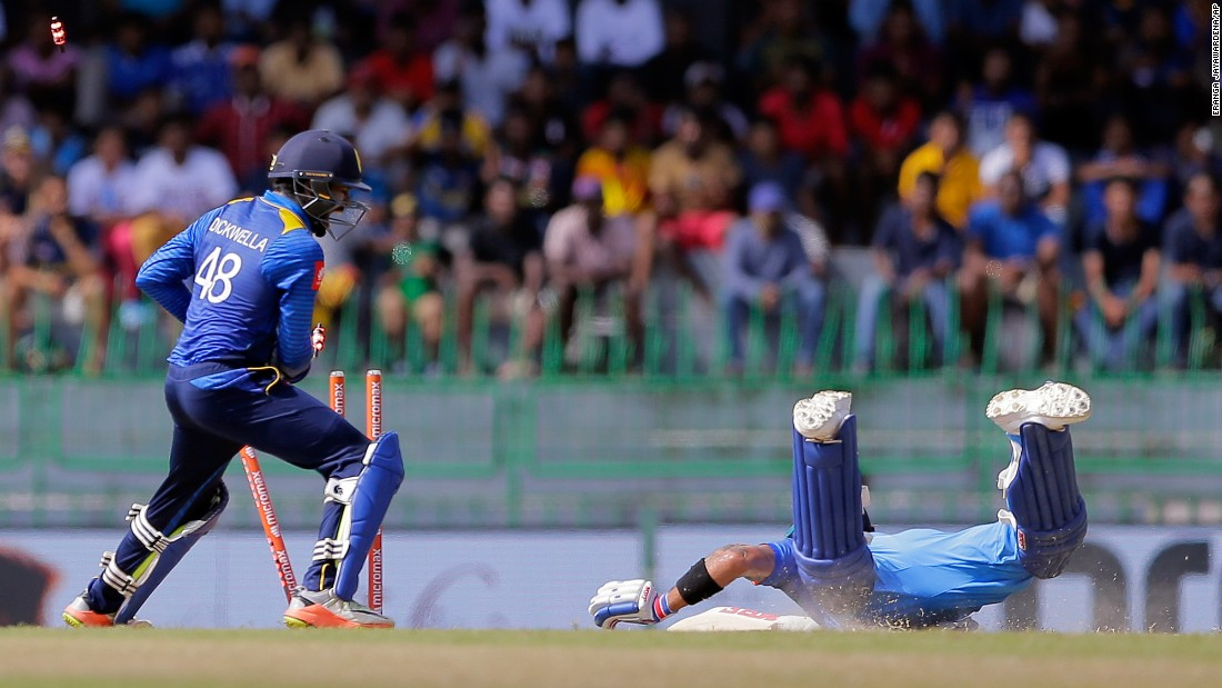 Sri Lankan wicketkeeper Niroshan Dickwella dislodges the stumps as Indian captain Virat Kohli successfully dives into the crease during a cricket match in Colombo, Sri Lanka, on Thursday, August 31. India swept Sri Lanka in five one-day internationals.