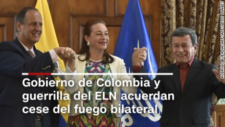 "Ecuadorean Foreign Minister Maria Fernanda Espinoza (C) raises the hands of chief negociators Juan Camilo Restrepo (L-for the Colombian government) and Pablo Beltran (for the ELN guerrilla) in Quito on September 4, 2017.  Colombia's government and the country's last active guerrilla group, the ELN, announced a ceasefire Monday, a key step toward sealing a ""complete peace"" to end Latin America's longest civil war. / AFP PHOTO / RODRIGO BUENDIA        (Photo credit should read RODRIGO BUENDIA/AFP/Getty Images)"