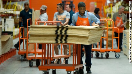 An employee pushes plywood to the checkout line at a Home Depot in West Palm Beach on Monday.