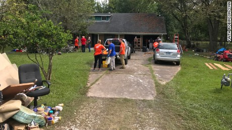 Volunteers gather outside Frances French's flood-damaged home.