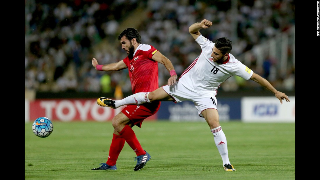 Tamer Haj Mohamad tries to shield the ball from Alireza Jahanbakhsh.