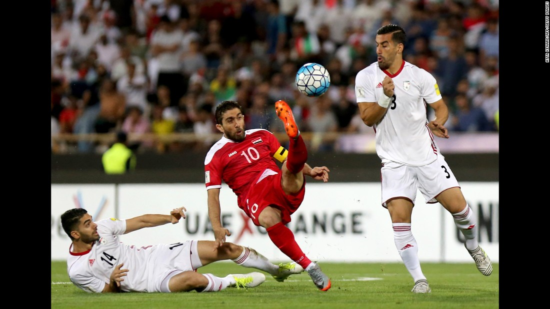 Firas Mohamad Al-Khatib competes with Iranian players Ali Karimi, left, and Ehsan Hajsafi. Iran has already clinched a spot in the World Cup.
