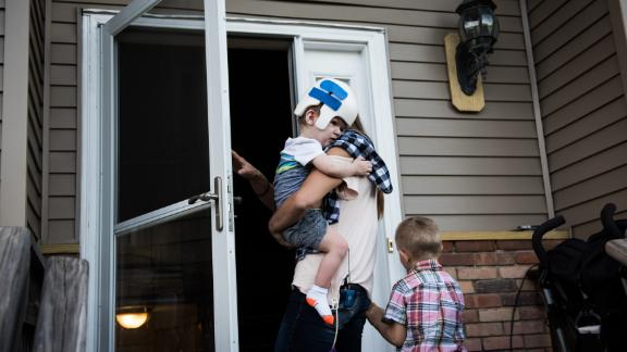 Nicole McDonald takes Anias into the family's new house for the first time with his older brother, Aza.