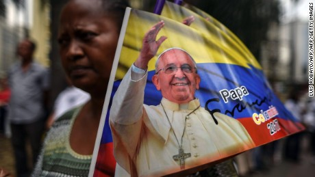 A woman holds a banner with the image of Pope Francis on September 2, 2017, in Cali, Colombia, during a Mass for the Pope's upcoming visit to Colombia. Pope Francis will make a special four-day visit to Colombia, from September 6 to 11, to add his weight to the process of reconciliation between the government and the FARC. / AFP PHOTO / LUIS ROBAYO        (Photo credit should read LUIS ROBAYO/AFP/Getty Images)