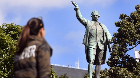 """People walk past a statue of Captain James Cook stands in Sydney's Hyde Park on August 25, 2017, as Prime Minister Malcolm Turnbull  labelled calls to change colonial-era monuments and the date of Australia Day, in attempts to better reflect the country's indigenous past, as a 'Stalinist' excercise in re-writing history. A cultural debate intensified this week when prominent indigenous commentator Stan Grant dubbed the inscription """"Discovered this territory 1770"""", on a Sydney statue of 18th century British explorer Capitan James Cook, a """"damaging myth"""". / AFP PHOTO / WILLIAM WEST        (Photo credit should read WILLIAM WEST/AFP/Getty Images)"""