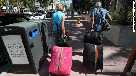 Tourists walk to catch a shuttle to a shelter in Miami Beach after the city announced a mandatory evacuation on Thursday ahead of Hurricane Irma.