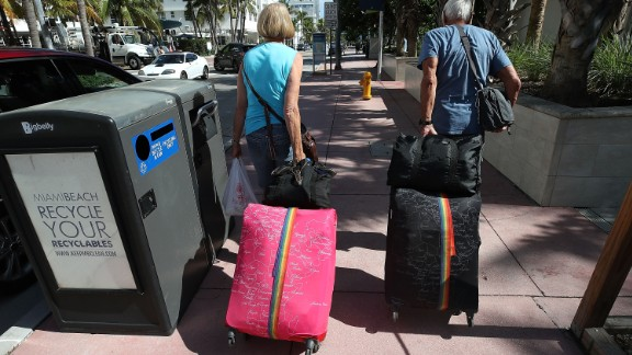 Tourist Bjorg Aasen and Arne Forsmo walk to catch a shuttle to a shelter as Miami Beach announced a mandatory evacuation.