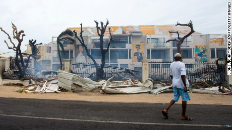 A man walks past damaged buildings and debris in St. Martin on September 6, after the passage of Hurricane Irma.