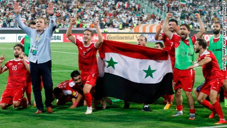 TOPSHOT - Syria's players celebrate at the end of their FIFA World Cup 2018 qualification football match against Iran at the Azadi Stadium in Tehran on September 5, 2017. / AFP PHOTO / ATTA KENARE        (Photo credit should read ATTA KENARE/AFP/Getty Images)