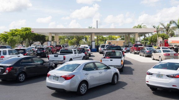 People wait in line at a Costco Gas Station in Miami on Thursday.