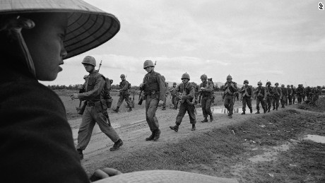 A Vietnamese woman watches U.S. Marines march toward defense positions in 1965. (AP Photo)