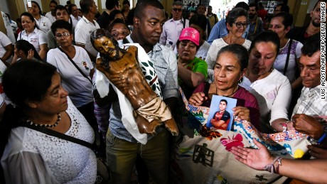 "Faithfuls hold the remains of the altar's Christ statue of the church of Bojaya Choco, upon arrival to Villavicencio Cathedral on September 7, 2017.   The Christ -that resisted an attack to Bojaya by FARC guerrillas in May 2002- will be blessed by Pope Francis in Villavicencio. Pope urged Colombians to avoid seeking ""vengeance"" for the sufferings of their country's half-century civil conflict as they work towards a lasting peace.  / AFP PHOTO / Luis Acosta        (Photo credit should read LUIS ACOSTA/AFP/Getty Images)"