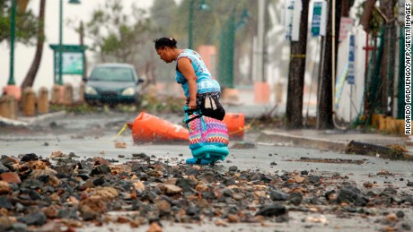 A woman pulls a suitcase through debris in Fajardo, Puerto Rico, on September 7.