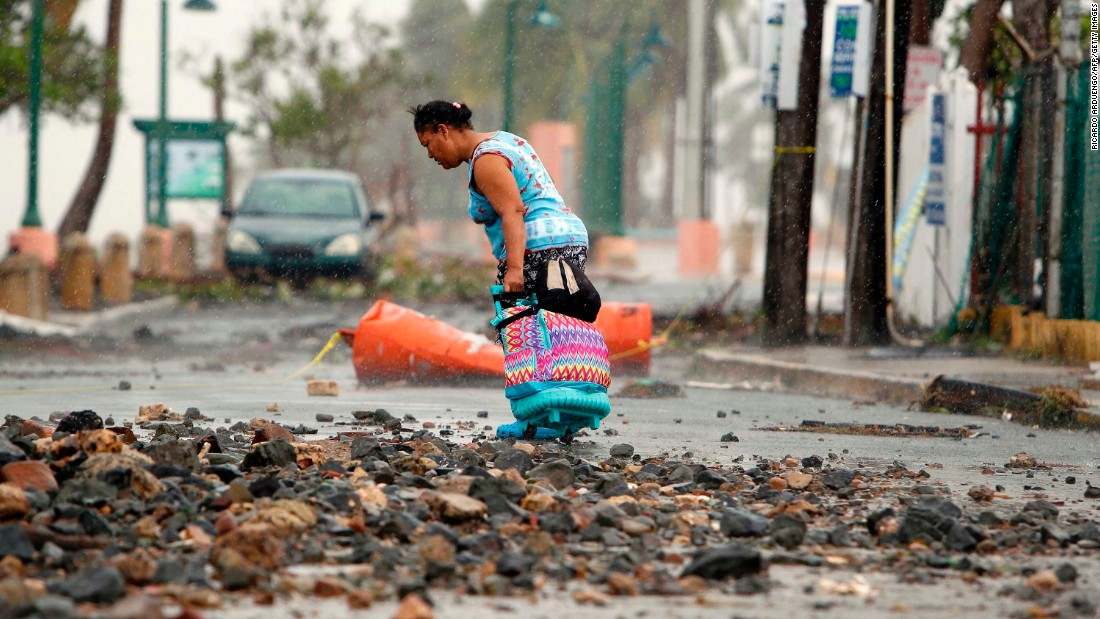 A woman makes her way through debris in Fajardo, Puerto Rico, on September 7.