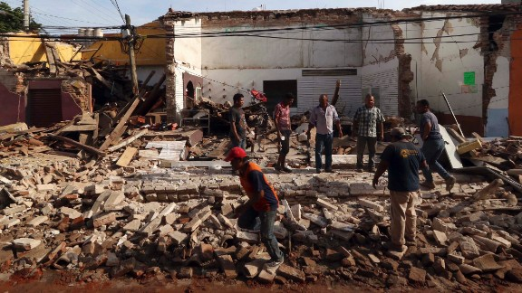 People stand on a building's rubble in Juchitan on September 8.