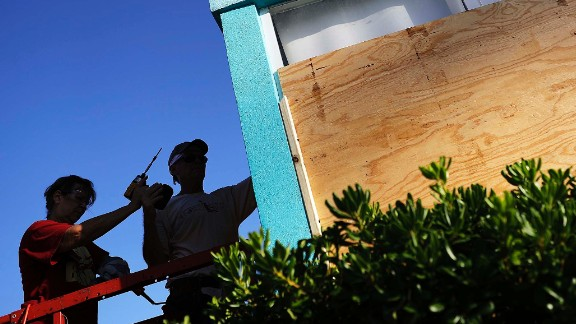Paulita Kundid, left, and her brother Mike board up their apartment building on Friday in Daytona Beach.