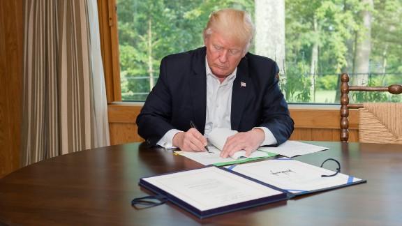 President Trump signs a $15 billion Hurricane Harvey relief bill on September 8 at Camp David.