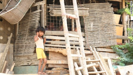 A young Rohingya child stands by a dwelling in the Arakanabad slum.