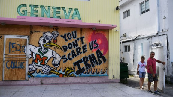 """People walk past a message reading """"You Don't Scare Us, Irma"""" on plywood used to protect the windows of a building as hurricane Irma approaches in Miami, Florida on Sept. 8, 2017."""