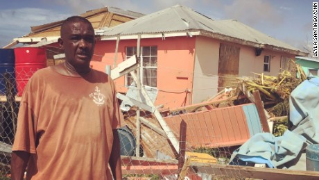 Elvis Burton stands outside his boarded-up home in Barbuda.