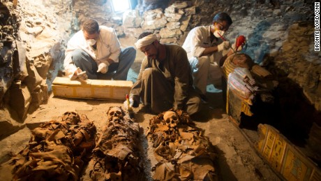 Researchers carefully examine the tomb.