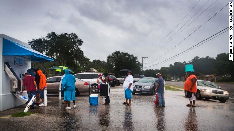 A local volunteer from Crossing Jordan Church helps other residents get ice from a vending machine on September 10 in Tampa.