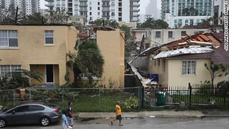 People walk past a building where the roof was blown off by Hurricane Irma in Miami, Florida.