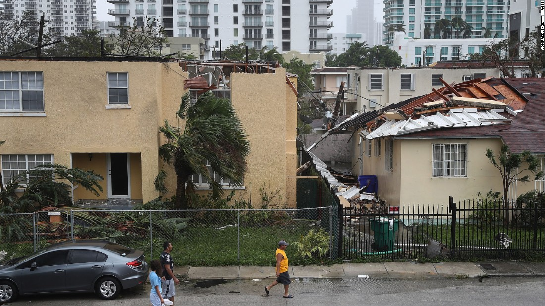 People walk past a building in Miami where the roof was blown off by Hurricane Irma on September 10.