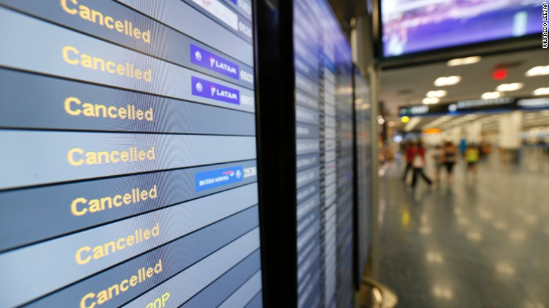 A monitor listing canceled flights at Miami International Airport is shown, Friday, Sept. 8, 2017 in Miami. Hurricane Irma scraped Cuba's northern coast Friday on a course toward Florida, leaving in its wake a ravaged string of Caribbean resort islands strewn with splintered lumber, corrugated metal and broken concrete. (AP Photo/Wilfredo Lee)