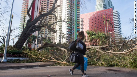 Estrella Palacios walks through debris caused by Hurricane Irma on Brickell Avenue in Miami, Florida, on September 11, 2017. / AFP PHOTO / SAUL LOEB        (Photo credit should read SAUL LOEB/AFP/Getty Images)